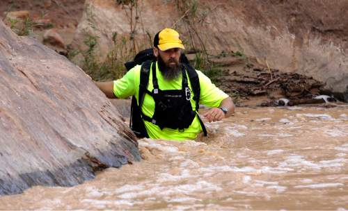 A member of a search and rescue team wades in to Virgin River during a search Wednesday, Sept. 16, 2015, in Zion National Park, near Springdale, Utah.  Seven hikers who entered a narrow desert canyon for a day of canyoneering became trapped when a flash flood filled the chasm with water, killing at least five of them in Zion National Park in southern Utah, officials said Wednesday.   (AP Photo/Rick Bowmer)