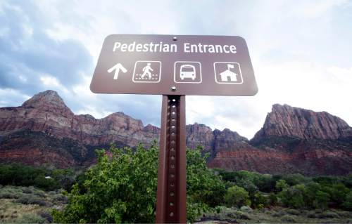A pedestrian sign stands at Zion National Park on Wednesday, Sept. 16, 2015, near Springdale, Utah. Authorities are searching for four people still missing after flash flooding killed several people in a Utah-Arizona border community and four others in Zion National Park. (AP Photo/Rick Bowmer)