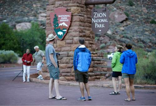 Visitors stand at the entrance of Zion National Park Wednesday, Sept. 16, 2015, near Springdale, Utah. Authorities are searching for four people still missing after flash flooding killed several people in a Utah-Arizona border community and others in Zion National Park. (AP Photo/Rick Bowmer)