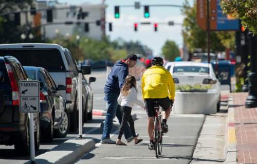Steve Griffin  |  The Salt Lake Tribune A bike rider yields to pedestrians in the new bike lanes on 300 South near State Street in Salt Lake City on Friday.