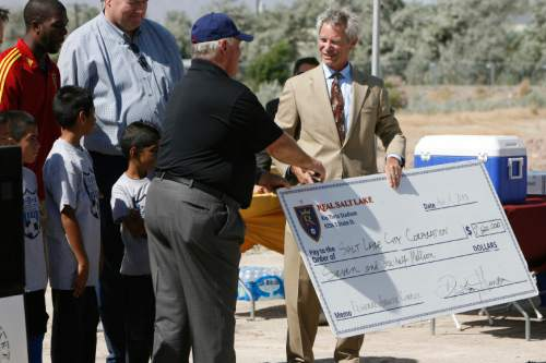 Francisco Kjolseth  |  The Salt Lake Tribune Mayor Ralph Becker, right, is all smiles after receiving a ceremonial check from Real Salt Lake (RSL) owner Dell Loy Hansen to re-start the construction on the City's voter-approved Regional Athletic Complex (RAC) with an RSL's gift of $7.5 million to help complete the project. The soccer complex property, near 2100 North Rose Park Lane, will have 16 new fields and is expected to be completed in the Summer of 2015.
