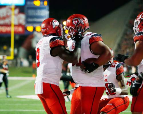 Utah defensive back Tevin Carter, left, celebrates defensive tackle Stevie Tu'ikolovatu's touchdown against Fresno State during the first half of an NCAA college football game in Fresno, Calif., Saturday, Sept. 19, 2015. (AP Photo/Gary Kazanjian)