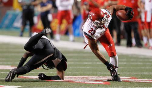 Utah running back Devontae Booker (23) avoids Fresno State defender Anthoula Kelly en route to a touchdown during the first half of an NCAA college football game in Fresno, Calif., Saturday, Sept. 19, 2015. (AP Photo/Gary Kazanjian)