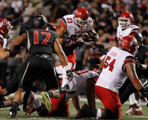Utah running back Devontae Booker carries against the Fresno State defense during the first half of an NCAA college football game in Fresno, Calif., Saturday, Sept. 19, 2015. (AP Photo/Gary Kazanjian)