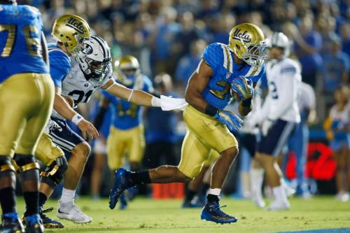 UCLA running back Nate Starks scores a touchdown past BYU linebacker Sae Tautu  during the the fourth quarter of an NCAA college football game, Saturday, Sept. 19, 2015, in Pasadena, Calif. UCLA won 24-23. (AP Photo/Danny Moloshok)