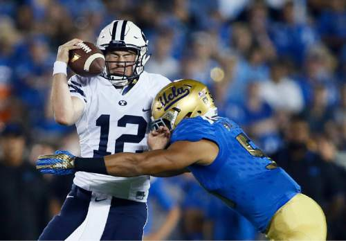 UCLA linebacker Aaron Wallace, right, sacks BYU quarterback Tanner Mangum during the first half of an NCAA college football game, Saturday, Sept. 19, 2015, in Pasadena, Calif. (AP Photo/Danny Moloshok)