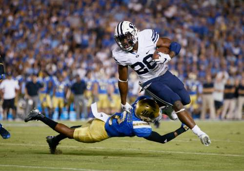 BYU running back Adam Hine breaks a tackle attempt from UCLA's Jaleel Wadood on his way to scoring a touchdown during the first half of an NCAA college football game Saturday, Sept. 19, 2015, in Pasadena, Calif. (AP Photo/Danny Moloshok)