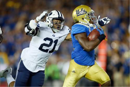 BYU linebacker Sae Tautu, left, dives to bring down UCLA running back Paul Perkins after a long gain during the first half of an NCAA college football game, Saturday, Sept. 19, 2015, in Pasadena, Calif. (AP Photo/Danny Moloshok)