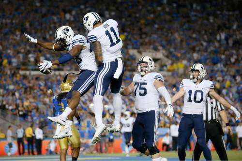 BYU running back Adam Hine, left, celebrates his touchdown with wide receiver Terenn Houk against UCLA during the first half of an NCAA college football game, Saturday, Sept. 19, 2015, in Pasadena, Calif. (AP Photo/Danny Moloshok)
