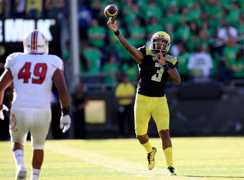 FILE - In this Sept. 5, 2015, file photo, Oregon quarterback Vernon Adams Jr. unleashes a pass during an NCAA college football game against Eastern Washington in Eugene, Ore. Adams  confirmed that he has a broken finger and says it's a game-time decision whether he'll start on Saturday against Georgia State. Vernon told reporters on Wednesday that he broke his finger in the season opener and it was bothering him in the Ducks' 31-28 loss at  Michigan State last weekend. (AP Photo/Ryan Kang, File)