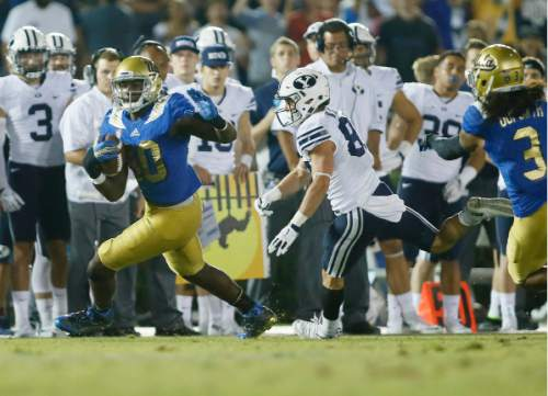 UCLA linebacker Myles Jack runs with the ball after intercepting the ball while BYU wide receiver Mitchell Juergens runs after him late in the fourth quarter of an NCAA college football game, Saturday, Sept. 19, 2015, in Pasadena, Calif. UCLA won 24-23. (AP Photo/Danny Moloshok)