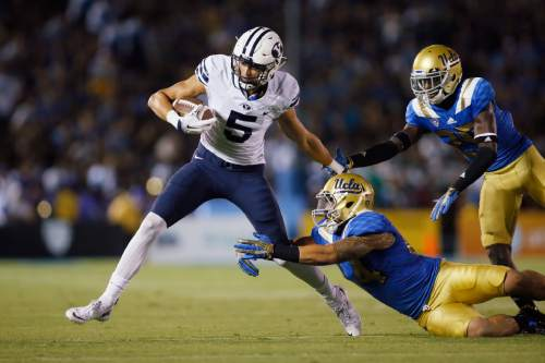 BYU wide receiver Nick Kurtz tries to avoid UCLA linebacker Isaako Savaiinaea, center, and defensive back Denzel Fisher, right, after a reception during the first half of an NCAA college football game, Saturday, Sept. 19, 2015, in Pasadena, Calif. (AP Photo/Danny Moloshok)