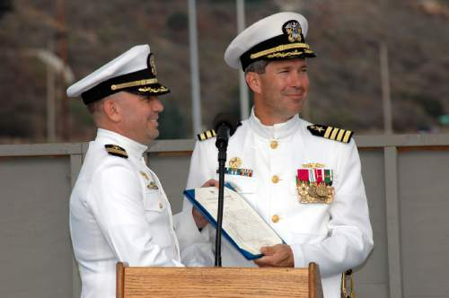 San Diego, Calif. (Oct. 26, 2005) – Cmdr. Tracy L. Howard, Commanding Officer, USS Salt Lake City (SSN 716), receives an award on behalf of the ship from Capt. Michael McLaughlin, Commander, Submarine Squadron 11 (COMSUBRON 11) during the inactivation ceremony for Salt Lake City at Naval Base Point Loma. Salt Lake City was launched on October 16, 1982 and commissioned on May 12, 1984. (U.S. Navy photo by Photographer's Mate 3rd Class Timothy F. Sosa.) (RELEASED)
