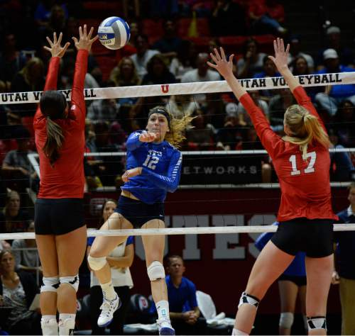 Francisco Kjolseth | The Salt Lake Tribune BYU's Veronica Jones threads the ball between Utah players Eliza Katoa, left, and Brenna DeYoung in the annual meeting between the schools' women's volleyball teams at Utah.