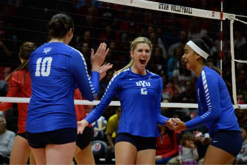 Francisco Kjolseth | The Salt Lake Tribune BYU's Cosy Burnett, center, celebrates a point with teammates as they battle Utah in the annual meeting between the schools' women's volleyball teams at Utah.
