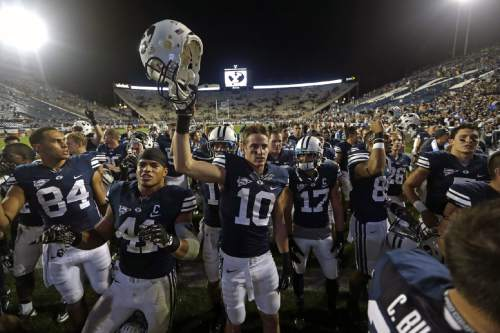 FILE - This Sept. 7, 2013, file photo, shows Brigham Young's Devin Mahina (84), Uani Unga (41) and Mitch Mathews (10) celebrating with other players following their NCAA college football game against Texas, in Provo, Utah. BYU has visions of mismatches across the field with the 2015 passing game. That begins with a pair of 6-foot-6 receivers nicknamed the Twin Towers. With running back Jamaal Williams gone for the season, Mitch Mathews and Nick Kurtz need to live up to the hype. (AP Photo/Rick Bowmer, File)
