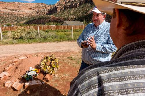 Trent Nelson     The Salt Lake Tribune Dee Barlow and Isaac Wyler stand over Walter Steed's grave at the Isaac W Carling Memorial Park Cemetery in Colorado City, Arizona on Wednesday.