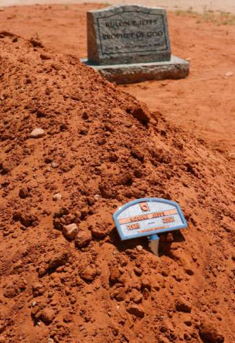 "Colorado City - A mound of dirt and small placard mark Norene Jeffs' simple grave, next to that of Rulon Jeffs, her husband. Friends and family members of Norene Jeffs gathered in the Colorado City cemetery to remember this plural wife, who had been buried the previous week in a secret funeral by members of the Fundamentalist Church of Jesus Chris of Latter-Day Saints (FLDS). Jeffs, who had been ""sealed"" to the previous FLDS prophet Rulon Jeffs (Warren Jeffs' father), was buried even before family members exiled from the secretive church were notified of her death. Trent Nelson/The Salt Lake Tribune; 7.09.2007"