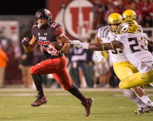 Rick Egan  |  The Salt Lake Tribune  Oregon Ducks linebacker Derrick Malone (22) gets a hand on Utah Utes running back Devontae Booker (23), in PAC-12 action, Utah vs. Oregon game, at Rice-Eccles Stadium, Saturday, November 8, 2014