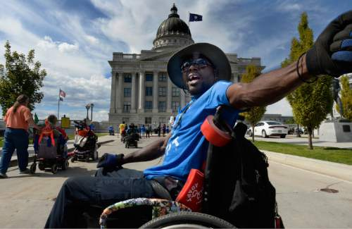 """Scott Sommerdorf      The Salt Lake Tribune Tony Brooks helped lead the chant of """"Our Homes - Not Nursing Homes!"""" as nearly 200 members of ADAPT, the national grassroots advocacy group for disability rights, marched to the Utah Capitol. Utahns with disabilities spoke about their struggles to achieve the freedom to choose where they can live independently, Sunday, September 26, 2015."""
