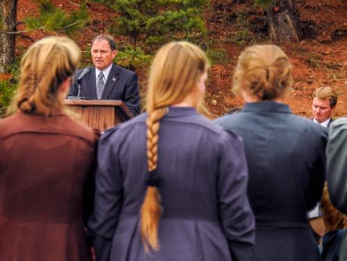 Trent Nelson  |  The Salt Lake Tribune Utah Governor Gary Herbert speaks at a memorial for the victims of a Sept.  14 flash flood. At right is Joseph Jessop, who lost two wives and seven children in the flood. The memorial was held in Maxwell Park in Hildale, Saturday Sept. 26, 2015.