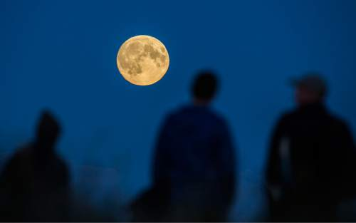 "People watch a full moon rising in Berlin, Germany, Sunday, Sept. 27, 2015. The full moon was seen prior to a phenomenon called a ""Super Moon"" eclipse that will occur during moonset on Monday morning, Sept. 28. (AP Photo/Gero Breloer)"