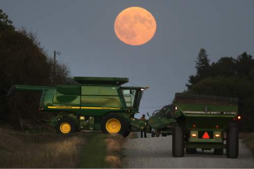 Clint Brown of Mason City, Iowa, mounts the head on his father's combine as the so-called supermoon rises on Sunday, Sept. 27, 2015. It was the first time Sunday since 1982 that a total lunar eclipse was combined with a supermoon. (Arian Schuessler/Globe-Gazette via AP) MANDATORY CREDIT