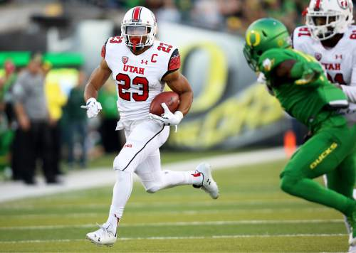 Utah running back Devontae Booker (23)  carries the ball during the first half of an NCAA college football game against Oregon, Saturday, Sept. 26, 2015, in Eugene, Ore. (AP Photo/Ryan Kang)
