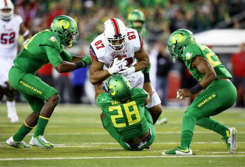 Utah tight end Siale Fakailoatonga (87) runs over Oregon linebacker Johnny Ragin III (28) during the second half of an NCAA college football game, Saturday, Sept. 26, 2015, in Eugene, Ore. (AP Photo/Ryan Kang)