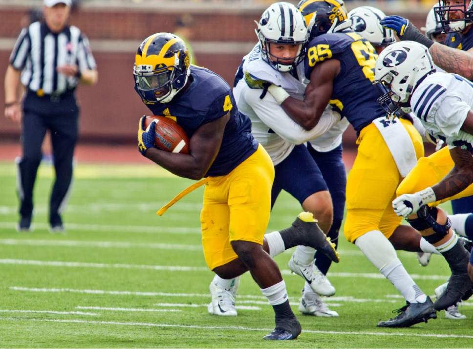 Michigan running back De'Veon Smith (4) breaks away from BYU defenders to rush across the field for a touchdown in the second quarter of an NCAA college football game in Ann Arbor, Mich., Saturday, Sept. 26, 2015. (AP Photo/Tony Ding)