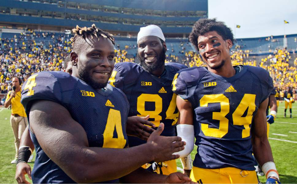 Michigan running back De'Veon Smith (4), greets teammates, tight end A.J. Williams (84) and defensive back Jeremy Clark (34), as they walk off the Michigan Stadium field after an NCAA college football game against BYU in Ann Arbor, Mich., Saturday, Sept. 26, 2015. Michigan won 31-0. (AP Photo/Tony Ding)