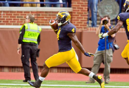 Michigan running back De'Veon Smith (4) celebrates his touchdown in the second quarter of an NCAA college football game against BYU in Ann Arbor, Mich., Saturday, Sept. 26, 2015. (AP Photo/Tony Ding)