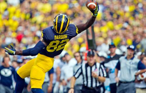 Michigan wide receiver Amara Darboh (82) makes a one-handed catch in the first quarter of an NCAA college football game against BYU in Ann Arbor, Mich., Saturday, Sept. 26, 2015. (AP Photo/Tony Ding)