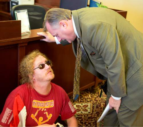 Rich Kane  |  The Salt Lake Tribune  Scott Nance (left) of disabled-rights organization ADAPT confers with Michael Mower, Gov. Herbert's Deputy Chief of Staff, during a protest by the group Tuesday afternoon September 29, 2015, inside the governor's office.