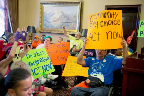 Rich Kane  |  The Salt Lake Tribune  Disability rights activists from the group ADAPT demonstrate inside Gov. Herbert's office Tuesday afternoon September 29, 2015. The group is calling for the governor to back the Community First Choice Option of the Affordable Care Act, which would make it easier for people with disabilities to stay in their homes.