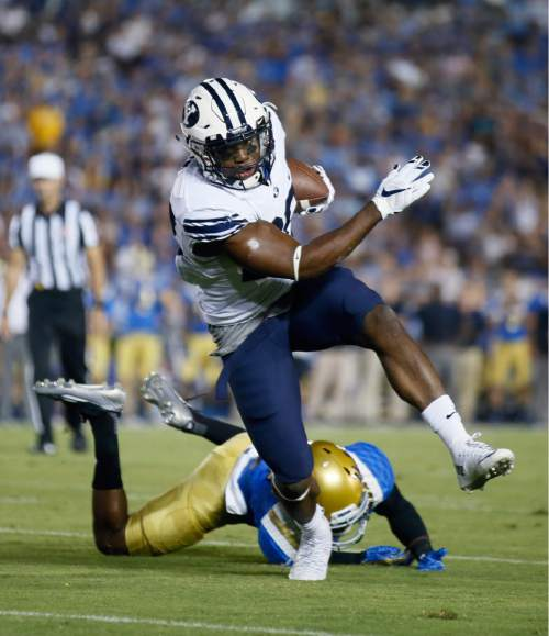 BYU running back Adam Hine breaks a tackle attempt from UCLA's Jaleel Wadood on his way to scoring a touchdown during the first half of an NCAA college football game, Saturday, Sept. 19, 2015, in Pasadena, Calif. (AP Photo/Danny Moloshok)