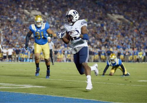 BYU running back Adam Hine, center, scores a touchdown after breaking a tackle attempt from UCLA's Jaleel Wadood, rear right, as UCLA defensive lineman Jacob Tuioti-Mariner runs toward him during the first half of an NCAA college football game, Saturday, Sept. 19, 2015, in Pasadena, Calif. (AP Photo/Danny Moloshok)