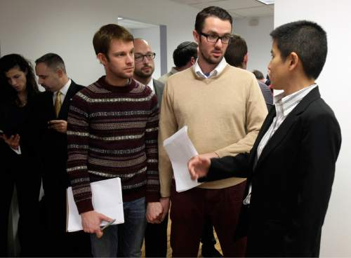 "Christine Sun, right, deputy legal director for the Southern Poverty Law Center, confers with Michael Ferguson, second right, and his partner Seth Anderson, before a news conference, in New York, Tuesday, Nov. 27, 2012. Ferguson, of Salt Lake City, is one of four gay men accusing a New Jersey organization of selling ""conversion therapy"" services promising to make them straight. Instead, they told the news conference that they were subjected to humiliations, including having to strip naked, or taking a baseball bat to effigies of their mothers.  Sam Wolfe, staff attorney for the SPLC is at background center. (AP Photo/Richard Drew)"