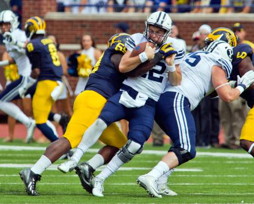 FILE - In this Sept. 26, 2015 file photo, BYU quarterback Tanner Mangum (12) is sacked by Michigan linebacker Noah Furbush (59) in the second quarter of an NCAA college football game in Ann Arbor, Mich.  Michigan is back in The Associated Press poll, ranked No. 22 in part because its defense is steadily improving under coach Jim Harbaugh.(AP Photo/Tony Ding)