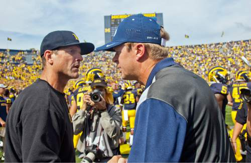 Michigan head coach Jim Harbaugh, left, speaks with BYU head coach Bronco Mendenhall, right, after an NCAA college football game in Ann Arbor, Mich., Saturday, Sept. 26, 2015. Michigan won 31-0. (AP Photo/Tony Ding)