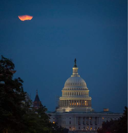 In this photo provided by NASA, a perigee full moon or supermoon is seen behind clouds over the United States Capitol, Sunday, Aug. 10, 2014, in Washington. (AP Photo/NASA, Bill Ingalls)