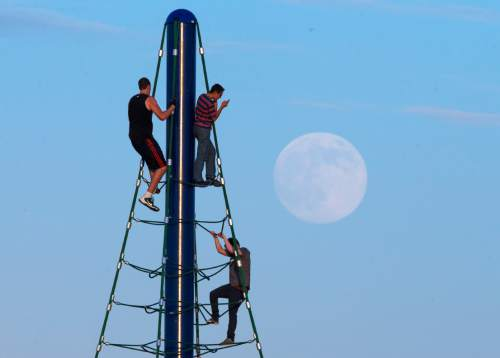 Michael Chow  |   AP file photo Men play on a climbing structure at Riverview Park in Mesa while the moon rises in Aug. 2014, a day before the supermoon is to appear.