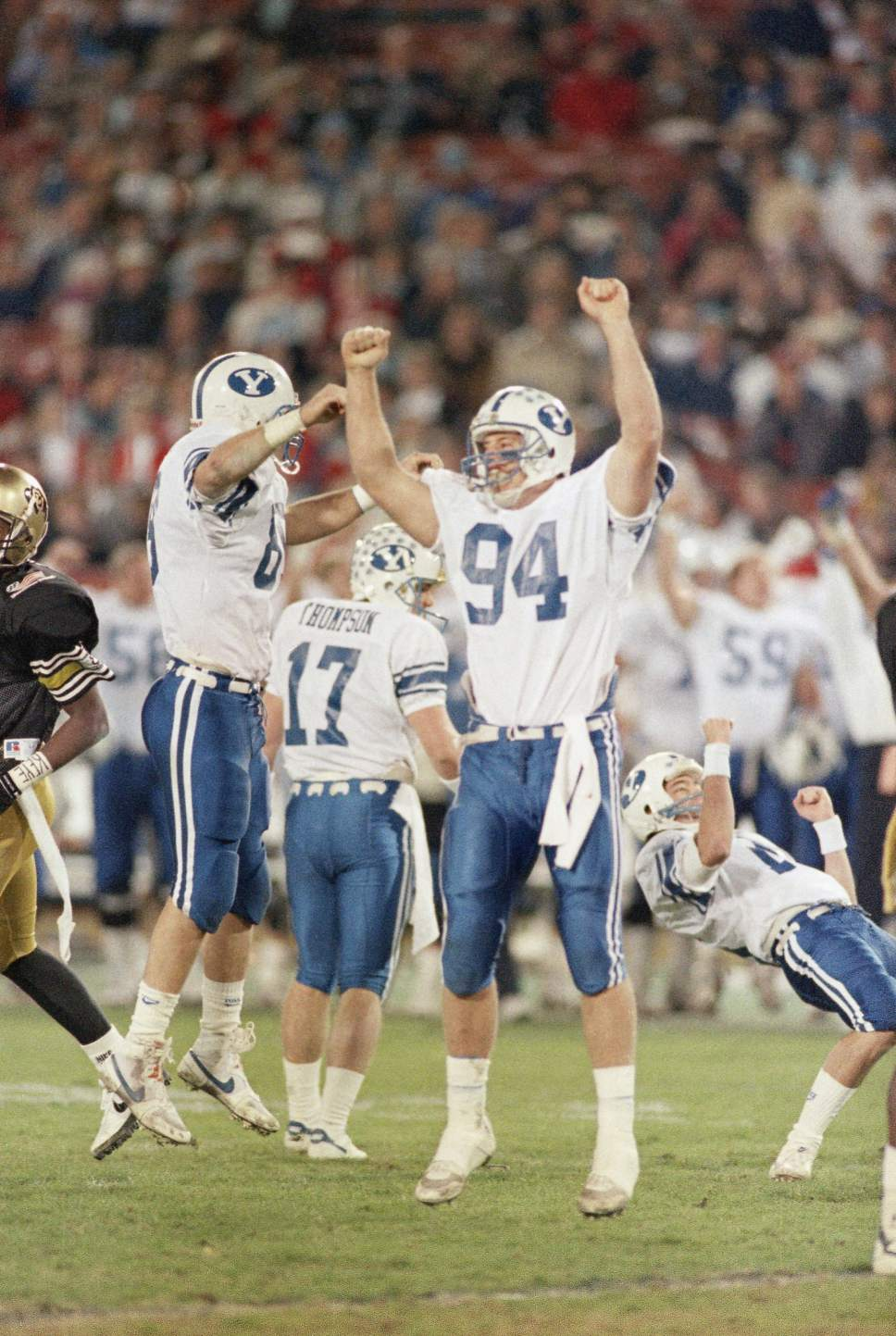 BYU kicker Jason Chaffetz (right) falls to the ground after kicking the winning field goal in the fourth quarter against Colorado at the Freedom Bowl in Anaheim, California, on Thursday, night, Dec. 30, 1988. Teammates Travis McBeth (left), Pat Thompson (17) and Chris Smith (94) also celebrate. BYU defeated Colorado 20-17. (AP Photo/Reed Saxon)