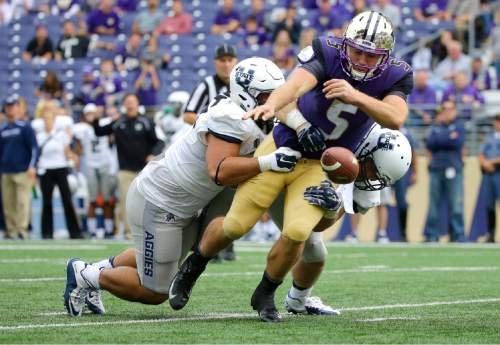 Washington quarterback Jeff Lindquist fumbles the ball as he is tackled by Utah State's Ricky Ali'ifua, left, and Kyler Fackrell, right, in the second half of an NCAA college football game, Saturday, Sept. 19, 2015, in Seattle. Washington won 31-17. Utah State's Jontrell Rocquemore recovered the fumble and ran it for a touchdown. (AP Photo/Ted S. Warren)