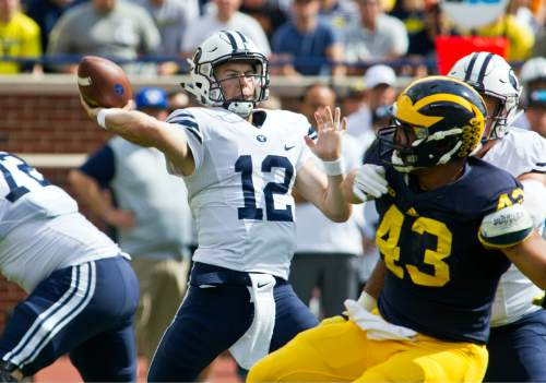 BYU quarterback Tanner Mangum (12) throws a pass from the pocket in the second quarter of an NCAA college football game against Michigan in Ann Arbor, Mich., Saturday, Sept. 26, 2015. Michigan won 31-0. (AP Photo/Tony Ding)