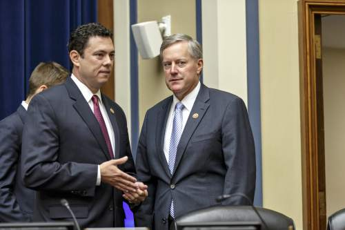 Rep. Jason Chaffetz, R-Utah, left, and Rep. Mark Meadows, R-N.C., confer as the House Oversight Committee meets to hear from U.S. Secret Service Director Julia Pierson about a security breach at the White House when a man climbed over a fence, sprinted across the north lawn and dash deep into the executive mansion before finally being subdued, on Capitol Hill in Washington, Tuesday, Sept. 30, 2014. (AP Photo/J. Scott Applewhite)
