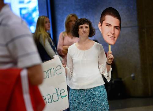 Scott Sommerdorf   |  The Salt Lake Tribune Angela Thomas, aunt of Ben Haacke, holds up a cutout of him as she and the Haacke family wait for their son to return at the Salt Lake International Airport earlier this month.