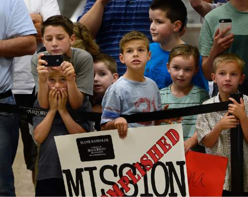 Scott Sommerdorf   |  The Salt Lake Tribune Brothers and friends of returning missionary Tyler Randolph anxiously await him near the escalators to the Delta baggage claim at the Salt Lake International Airport, Wednesday, September 9, 2015.