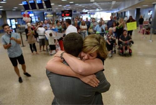 Scott Sommerdorf   |  The Salt Lake Tribune As then rest of the large group of family and friends watch and make pictures, Sheri Randolph hugs her son Tyler who has just returned from his mission to Peru at the Salt Lake International Airport, Wednesday, September 9, 2015.
