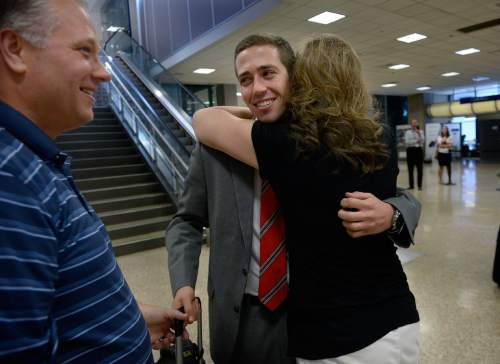 Scott Sommerdorf   |  The Salt Lake Tribune Father Wally Randolph, left, looks on as Sheri Randolph hugs her son Tyler who has just returned from his mission to Peru at the Salt Lake International Airport, Wednesday, September 9, 2015.